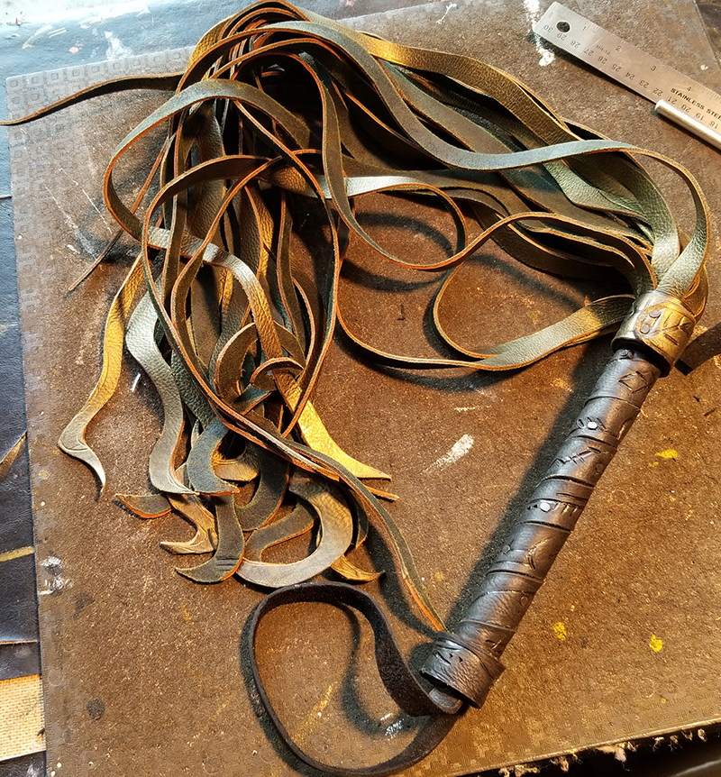 A leather flogger featuring a sigil-carved handle and tentacles instead of straight tails