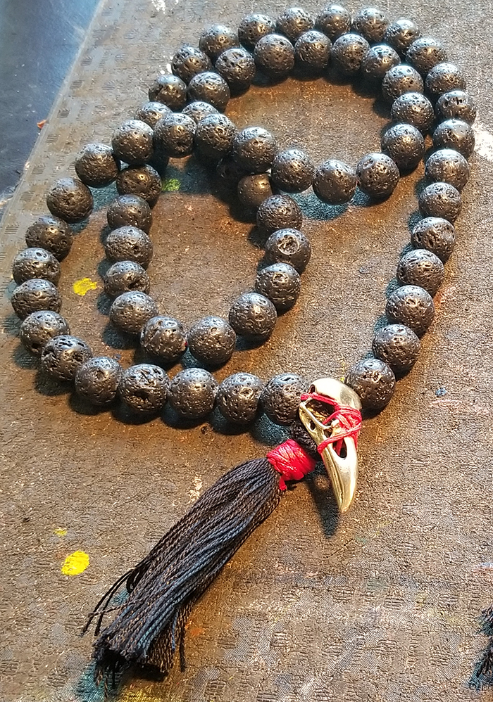 A prayer-bead mala made from lava with a crow skull focal bead