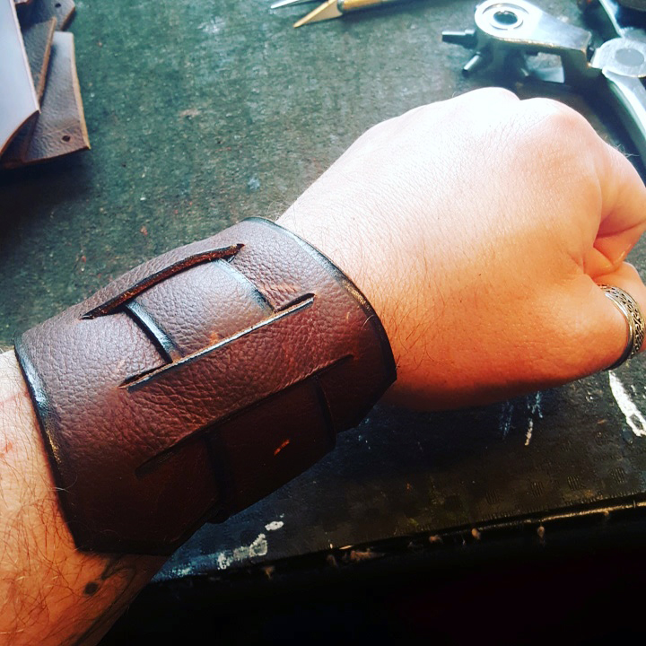 Scavenger Wrap- a leather wristwrap designed to tension-lock itself on the wearer's wrist